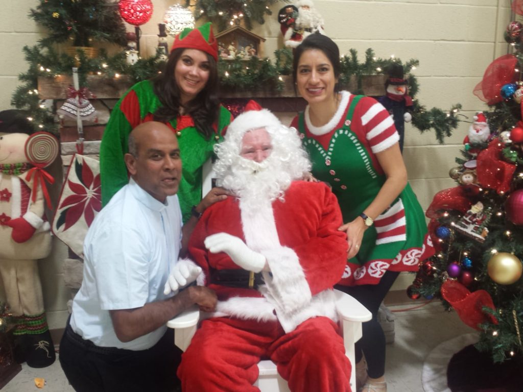 Fr. Gaspar Masilamani with Santa and two Elves