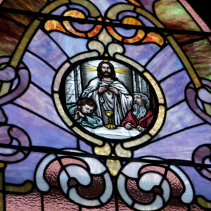 Stained glass of Jesus Christ and two apolstles at the Last Supper in Sacred Heart Catholic Church in Springfield MO