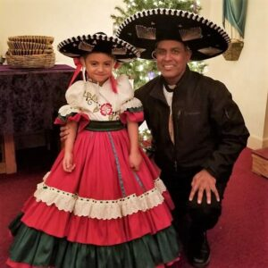 Fr. Gaspar Masilamani in a sombrero and a little girl in traditional Mexican clothes in front of a Christmas tree